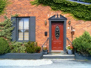 A red door with beveled glass insert surrounded by Georgian style framing.