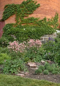 Brick tower covered with ivy with spring garden in front.