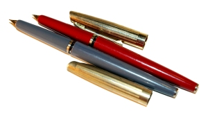 Vintage fountain pens - one gray, one red; both with gold caps.