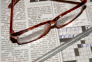Crossed Words - crossword puzzle and glasses.