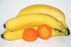 Bananas and oranges over white background.