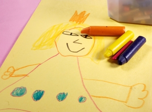 Crayons with children\'s drawing.