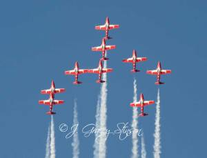 Snowbirds in flight - red planes against a blue sky.