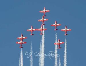 Snowbirds in flight - red planes against a blue sky.