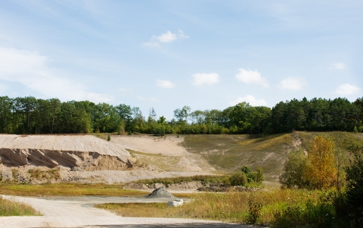 Open Gravel Pit - an open-mining gravel pit with piles of sand hidden in the rural countryside.