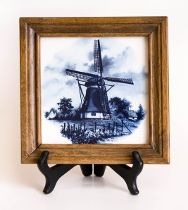 Delft Blue ceramic tile in wooden frame. Tile has windmill scene in blue.