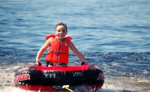 boy having fun tubing, and wearing his life jacket