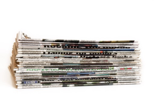 Newspaper Pile - stack of newspapers with folded side out.