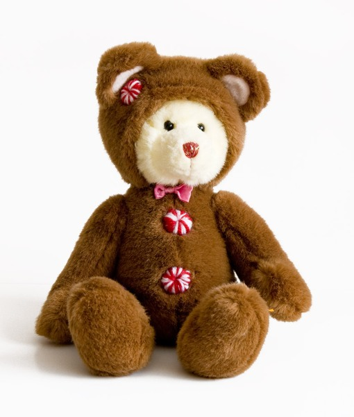 Fuzzy teddy with white face, brown coat and candy striped buttons.